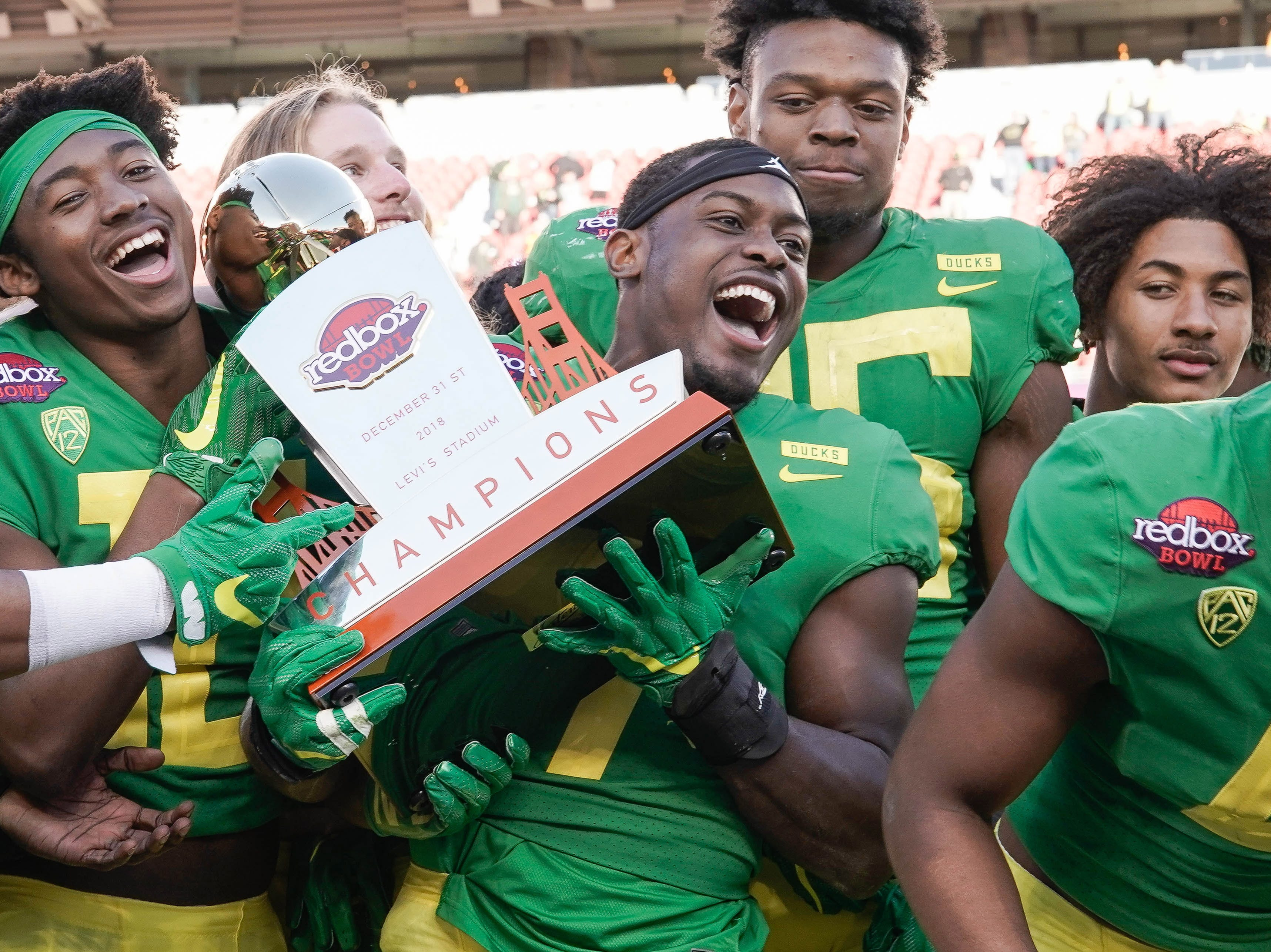 Oregon Ducks safety Ugochukwu Amadi (7) and teammates celebrate with the trophy after defeating the Michigan State Spartans in the Redbox Bowl.