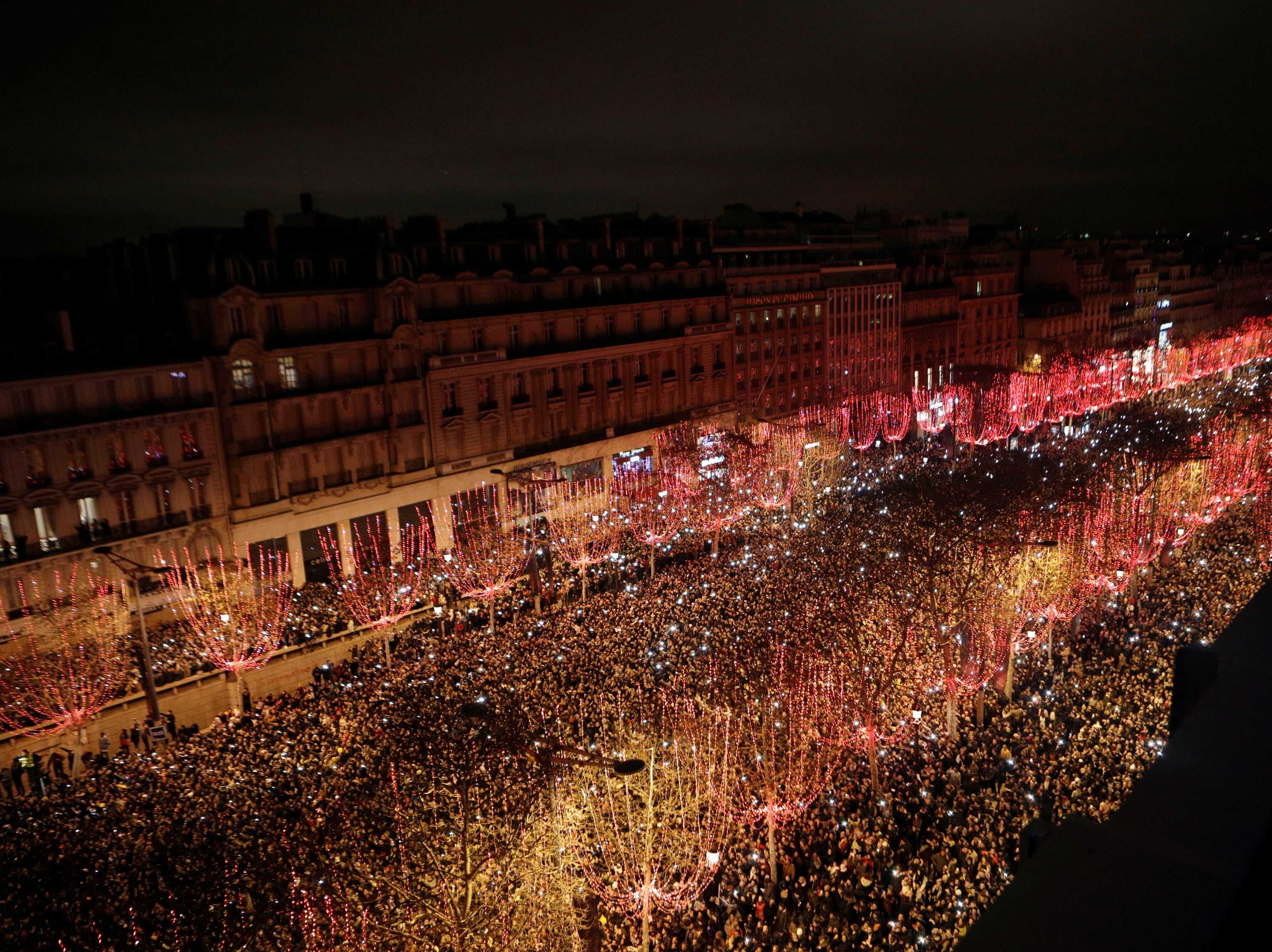 Spectators gather to attend the New Year's Day celebrations on the Champs Elysees, in Paris, Tuesday, Jan. 1, 2019.