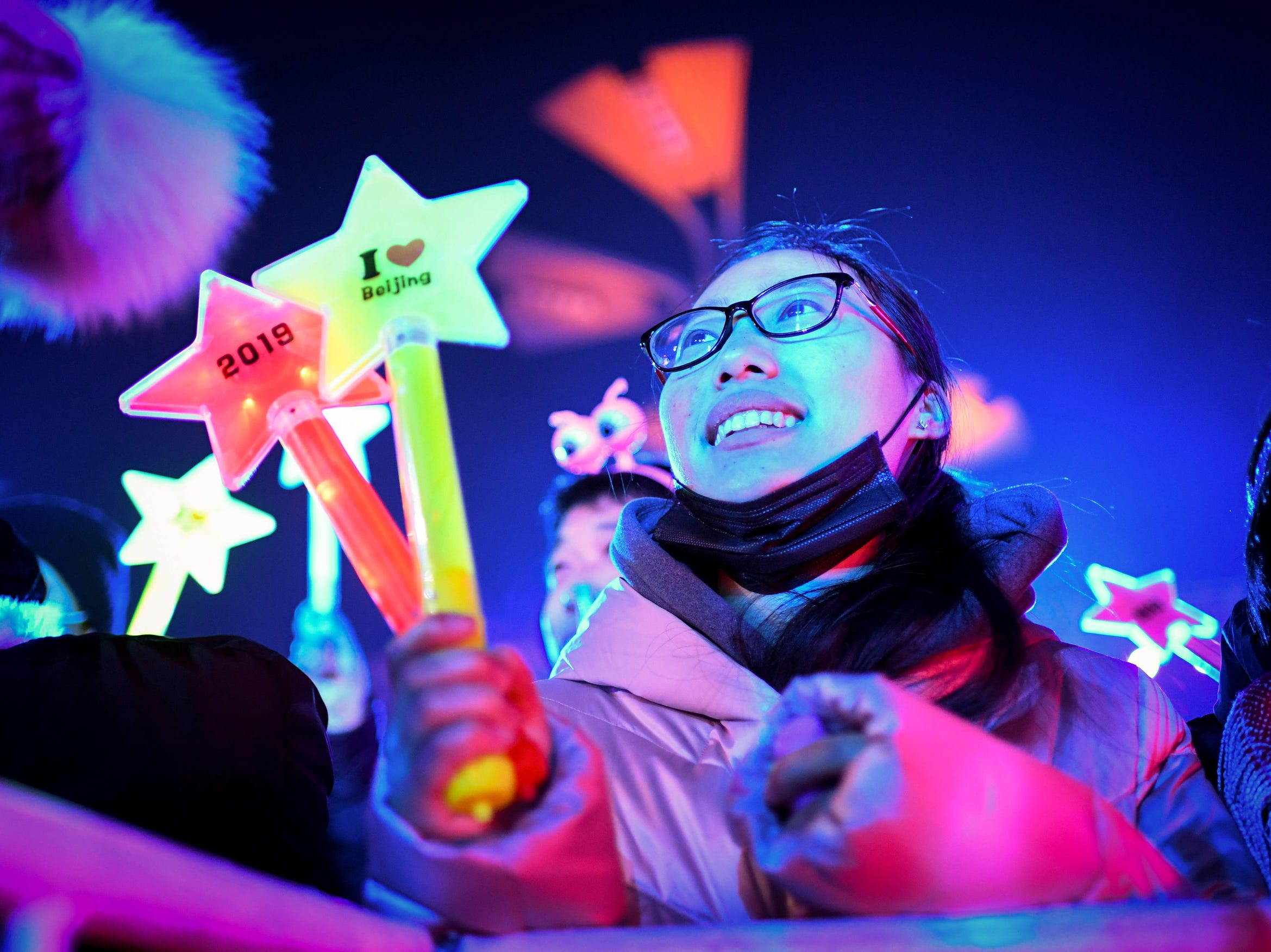 A woman looks on as she waits for celebrating the New Year during a New Year's Eve countdown event in front of Beijing's National Stadium, known as the Bird's Nest, in Beijing.