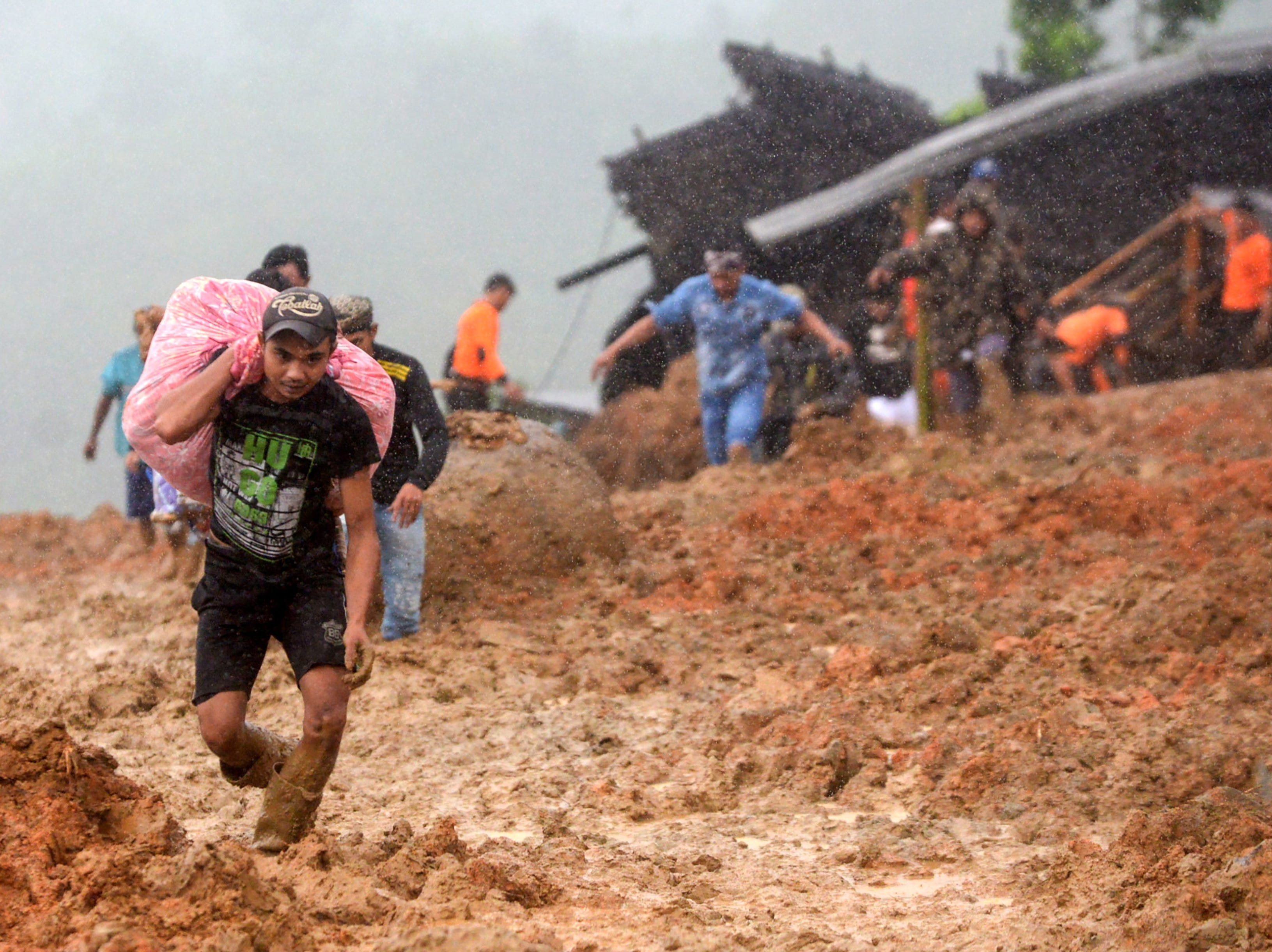 Residents evacuate their homes as rescue workers search for survivors at the site of a landslide triggered by heavy rain in Sukabumi, West Java province on Jan. 1, 2019.