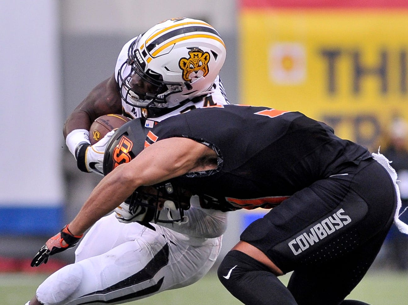 Missouri Tigers running back Larry Rountree III (34) carries the ball against Oklahoma State Cowboys safety Kolby Peel (31) during the first half in the Liberty Bowl.