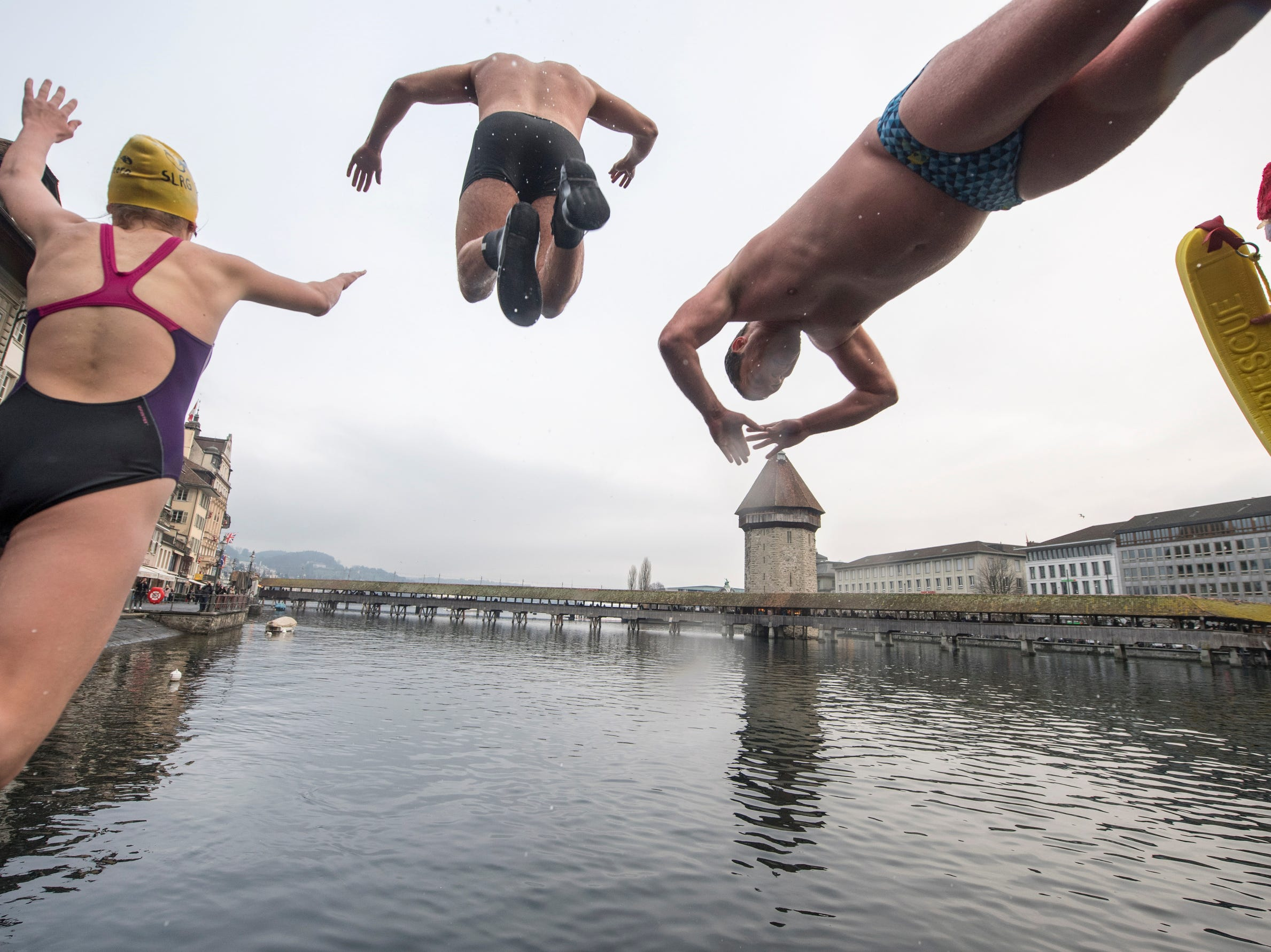 Approximately 40 lifeguards and swimmers of the Swiss Life Saving Society SLRG Lucerne Section celebrate New Year's Eve together with a jump into the Reuss river in the old town of Lucerne, Switzerland.