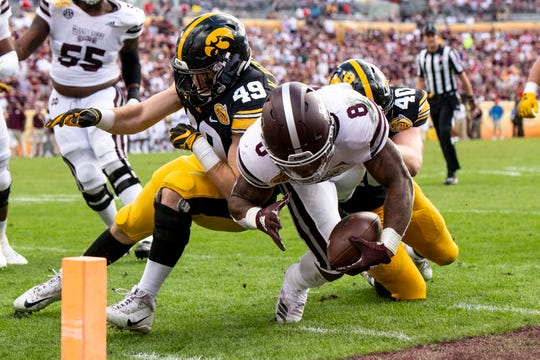 Jan 1, 2019; Tampa, FL, USA; Mississippi State Bulldogs running back Kylin Hill (8) runs the ball as Iowa Hawkeyes linebacker Nick Niemann (49) and defensive end Parker Hesse (40) defend during the third quarter in the 2019 Outback Bowl at Raymond James Stadium. Mandatory Credit: Douglas DeFelice-USA TODAY Sports