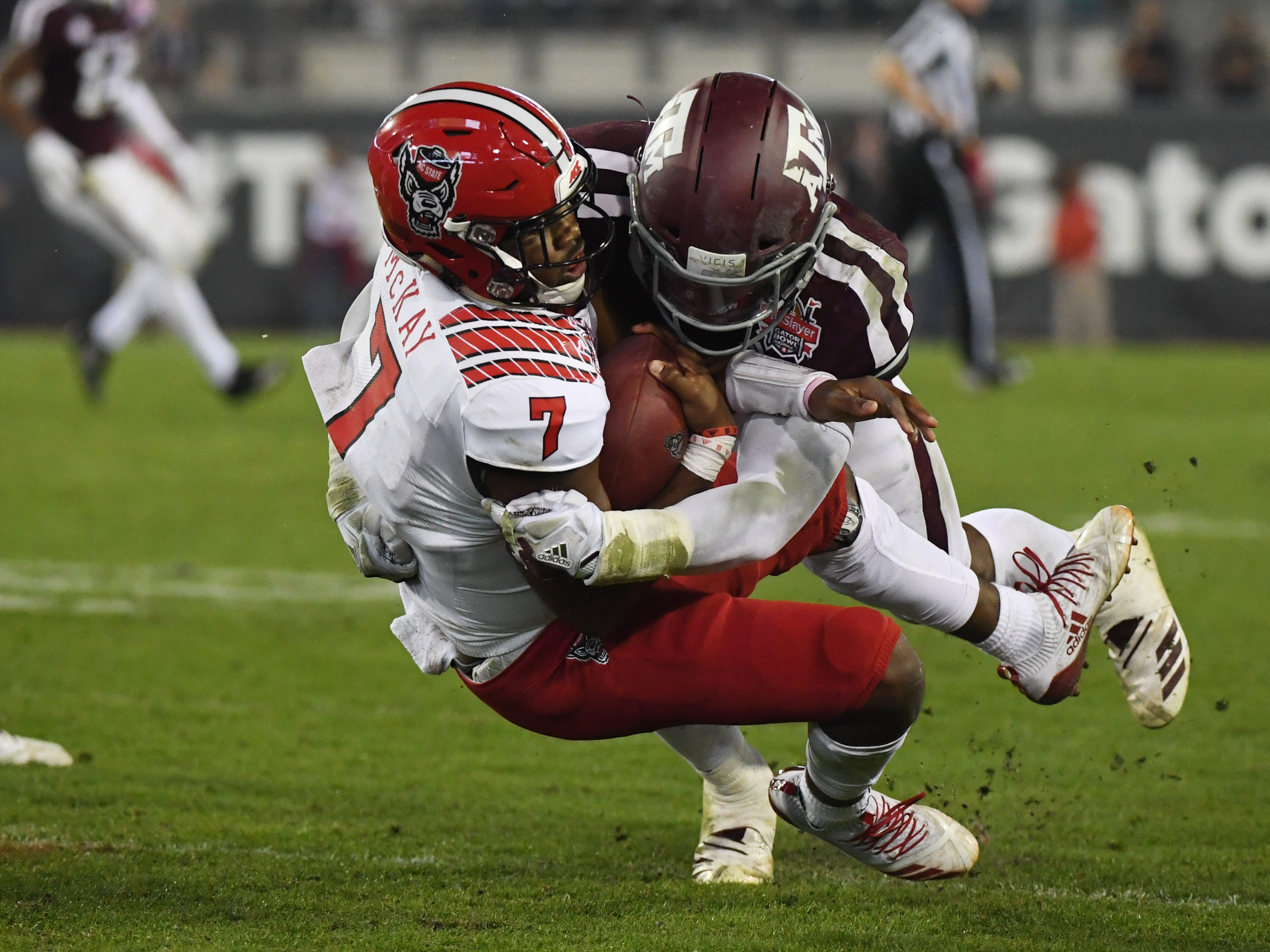 Texas A&M Aggies linebacker Buddy Johnson (1) tackles North Carolina State Wolfpack quarterback Matthew McKay (7) during the forth quarter of the Gator Bowl.