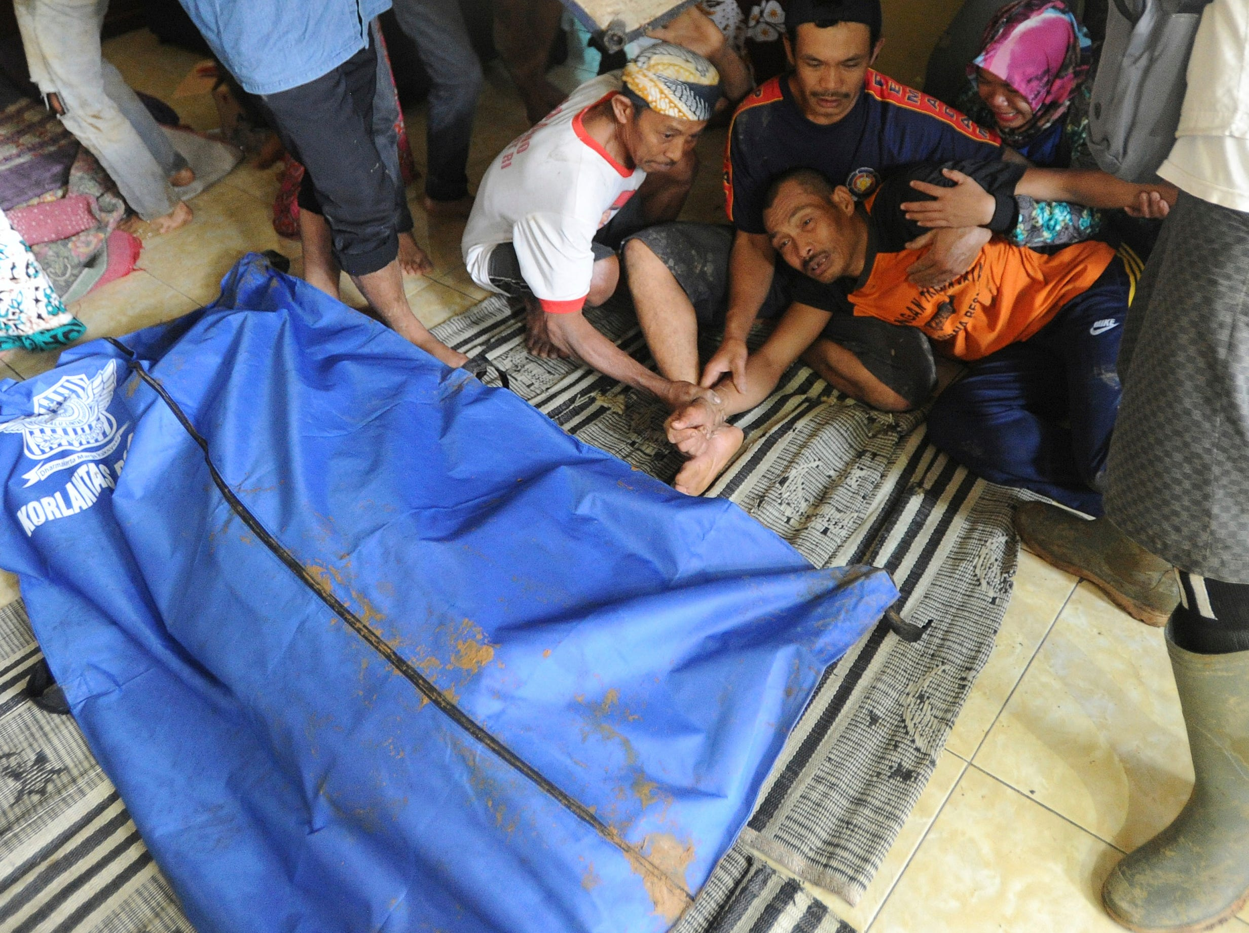 A man reacts near a body bag containing the body of his relative who was killed by a landslide in Sirnaresmi, West Java, Indonesia, Tuesday, Jan. 1, 2019. The landslide triggered by torrential rain has killed a number of people and left dozens others missing on Indonesia's main island of Java.