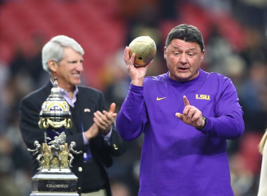 LSU Tigers head coach Ed Orgeron celebrates with the trophy after defeating the UCF Knights in the Fiesta Bowl.