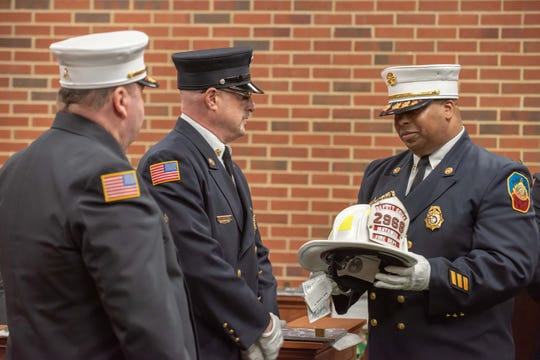01/01/19- Outgoing chief Rich Michitsch (center) presents Freddy Benjamin with his new helmet as 2nd Deputy Chief  of Matawan Fire Department.