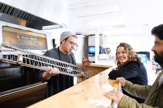Patricio Vera, co-owner and manager of Conosur, shows Mackensy Lunsford and Meherwan Irani a part from his rotisserie oven in Mills River Nov. 29, 2018.