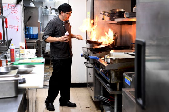 Sergio Casto, chef and co-owner at Conosur in Mills River, cooks up a dish in the kitchen Nov. 29, 2018.