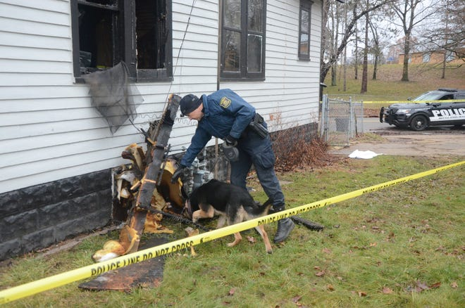Trooper Joel Service and his dog, Baki, inspect some of the debris from the fire at 250 Graves Ave. on Tuesday. Howard Gillette was found shot to death inside the house.