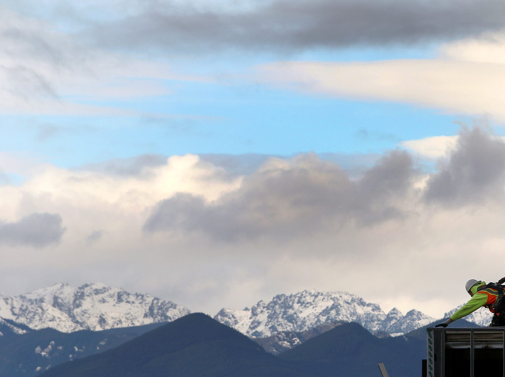 The Olympic Mountains peek out from the clouds on a cold day in Silverdale, behind construction workers at the Harrison Medical Center in Silverdale on Wednesday, January, 2, 2018.