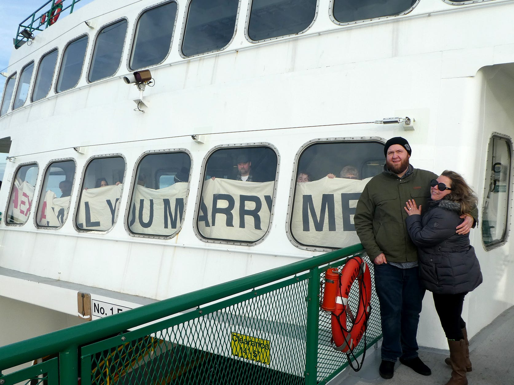 Friends and family hold up a will you marry me banner for Josh Batway and Alexia Haney of Seattle on the Kaleetan ferry ride from Seattle to Bremerton on Tuesday, January 1, 2019. He proposed to her on the ferry on their way to Aldberbrook on the Hood Canal.