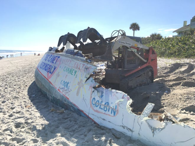 "A heavy equipment operator dismantles Cuki the ""ghost ship"" Wednesday morning at Spessard Holland South Beach Park."