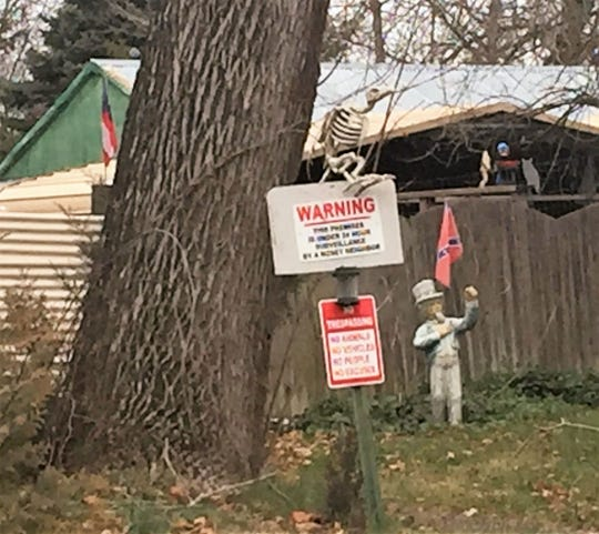 A statue of Uncle Sam holds a Confederate flag near a no-trespassing sign at the Winslow home of Michael Speece.