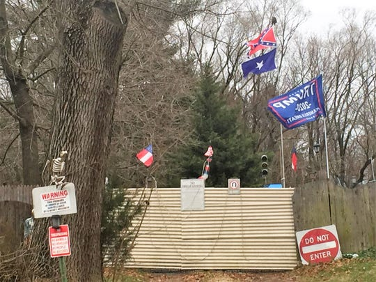 A Confederate flag and a Trump 2020 sign flutter over the backyard of Michael Speece's home in Winslow.