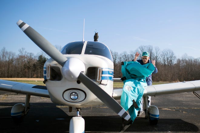 Pilot William Breuer, 94, removes a tarp from his 1963 Piper Cherokee 180 Thursday, Dec. 27 at the Flying W Airport in Medford, N.J.