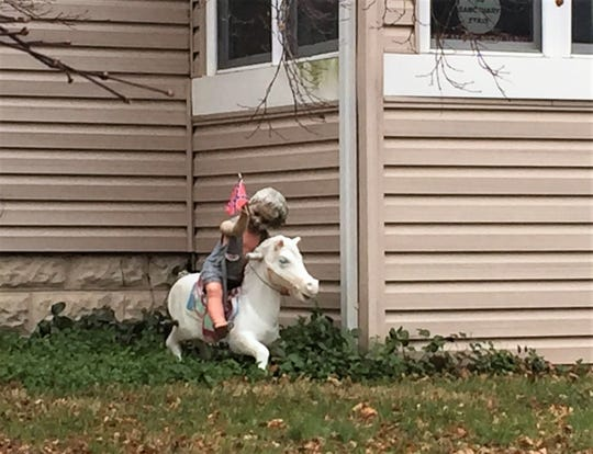 A display outside a Winslow home includes a small boy riding a carousel pony and holding a Confederate flag.