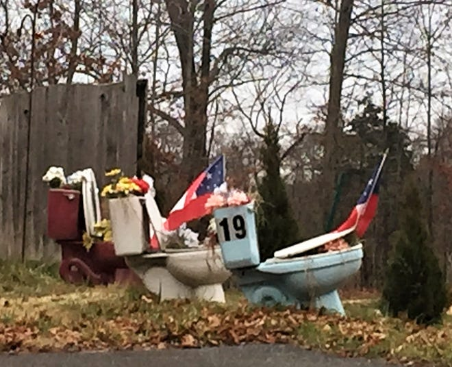 Three toilets hold plastic flowers and small flags outside the Winslow home of Michael Speece.