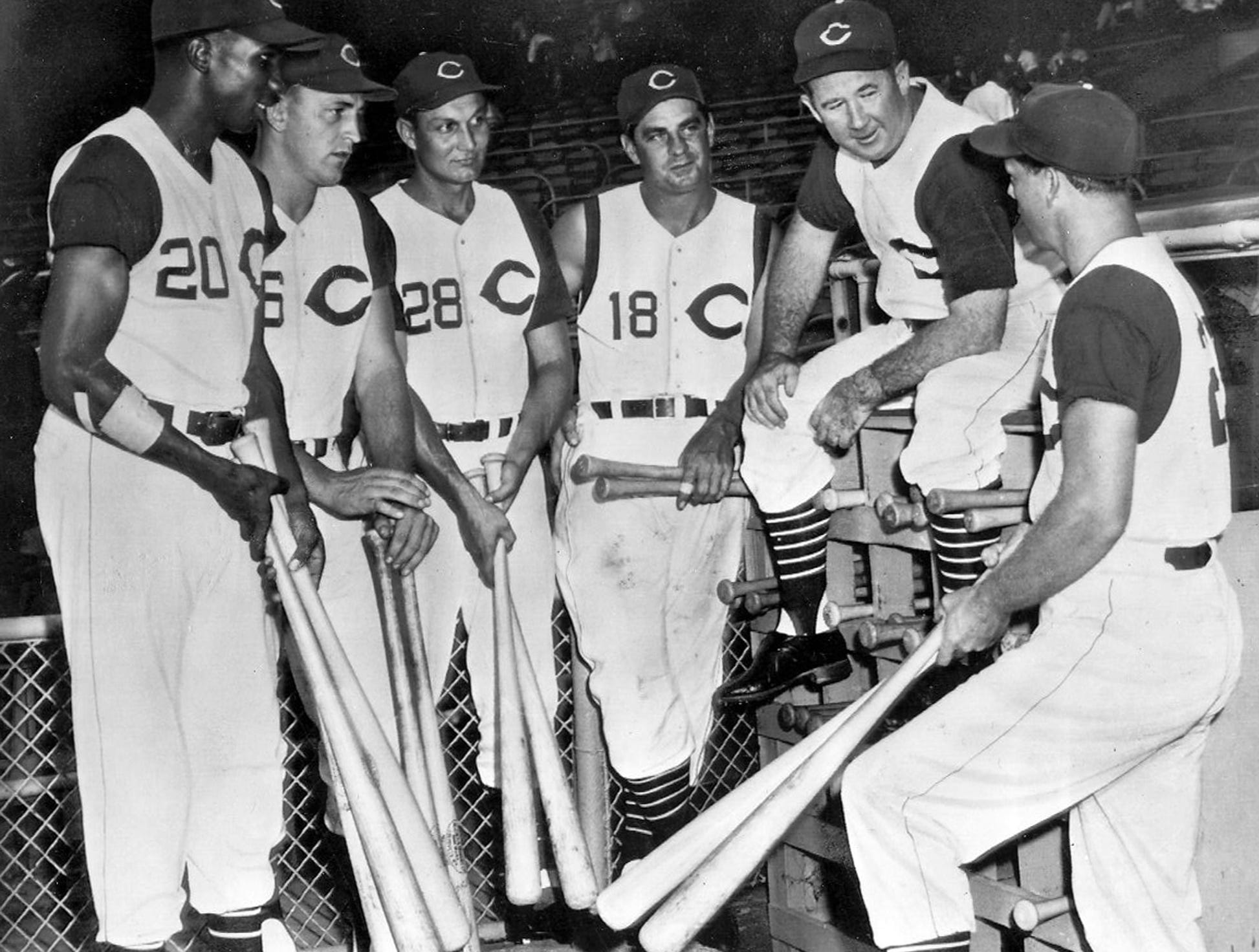 Cincinnati Redlegs manager Birdie Tebbetts perches on bat rack at Crosley Field and holds bull session with his heavy sluggers who have helped him put his team in the front at mid-season in the 1956 National League race. The heavy hitters are, left to right, Frank Robinson, Ed Bailey, Wally Post, Ted Kluszewski and Gus Bell. All except Post played in the All-Star game and did their share to bring victory to the team. AP Photo