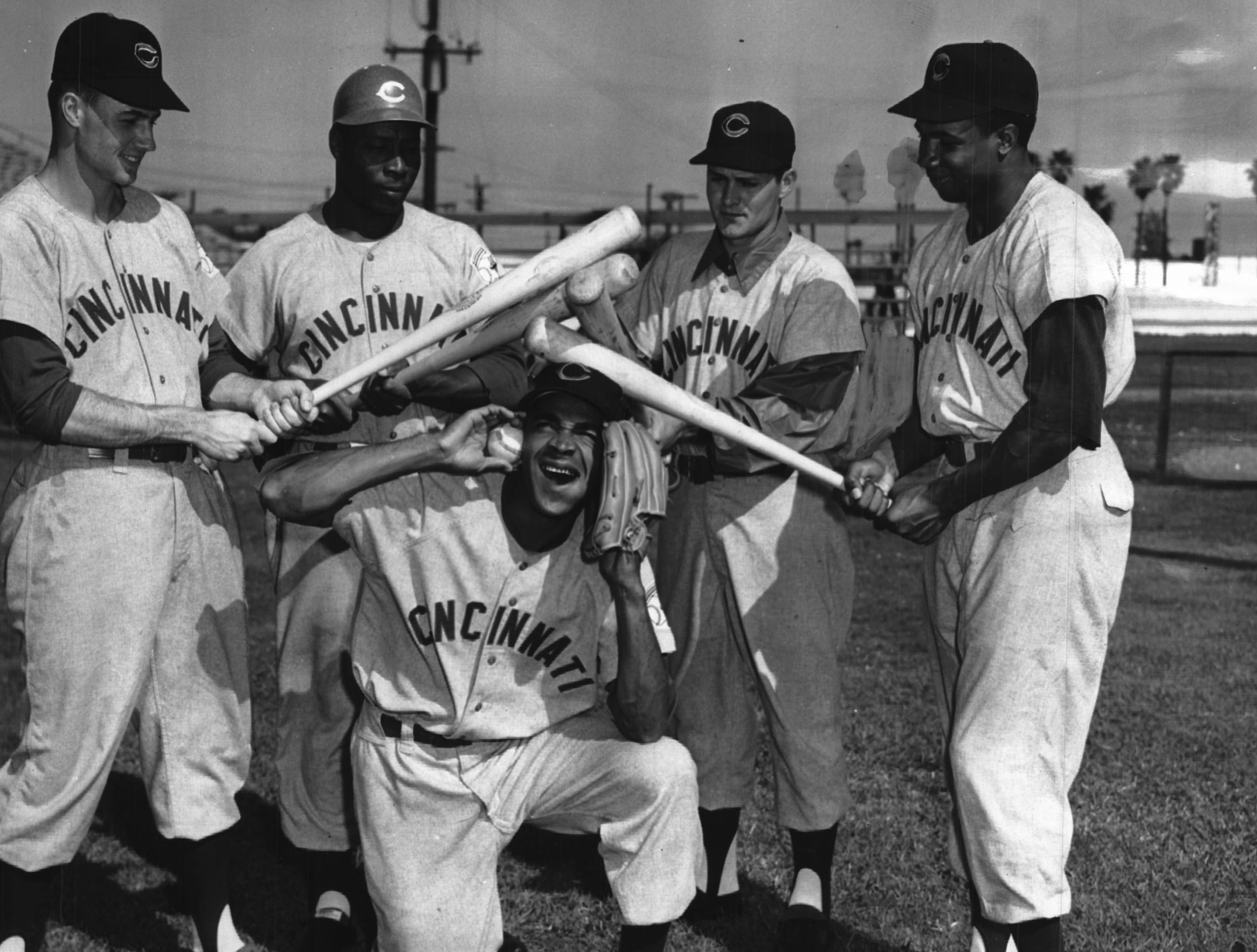 Chuck Harmon is surrounded by teammates who are trying out for the starting left field post with the Cincinnati Reds. Standing, left to right, are Billy Werber Jr., Bob Thurman, Bob Hazle and Frank Robinson.