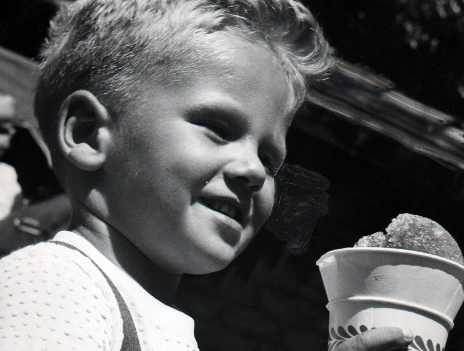 This unidentified boy enjoys a snow cone during warm weather.