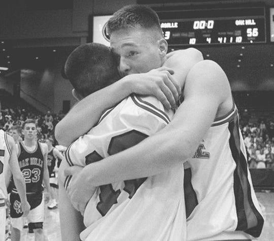 La Salle's Dave Esterkamp, right, hugs teammate Craig Conley following the Lancers' win over Oak Hills in Dayton.