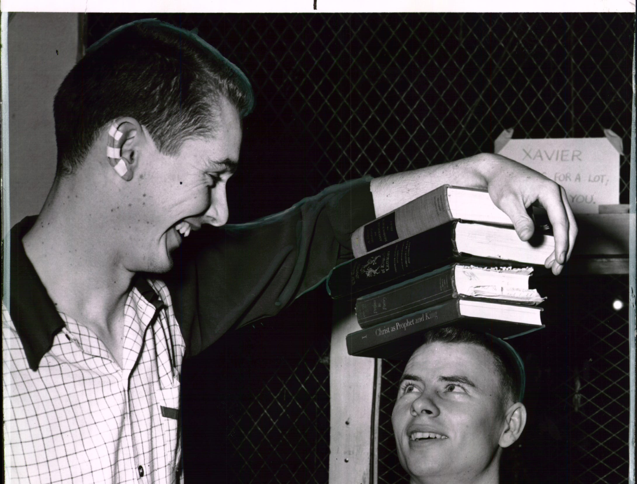 Xavier University basketball player Jim Boothe balances books on his head with Stu Courchainel.
