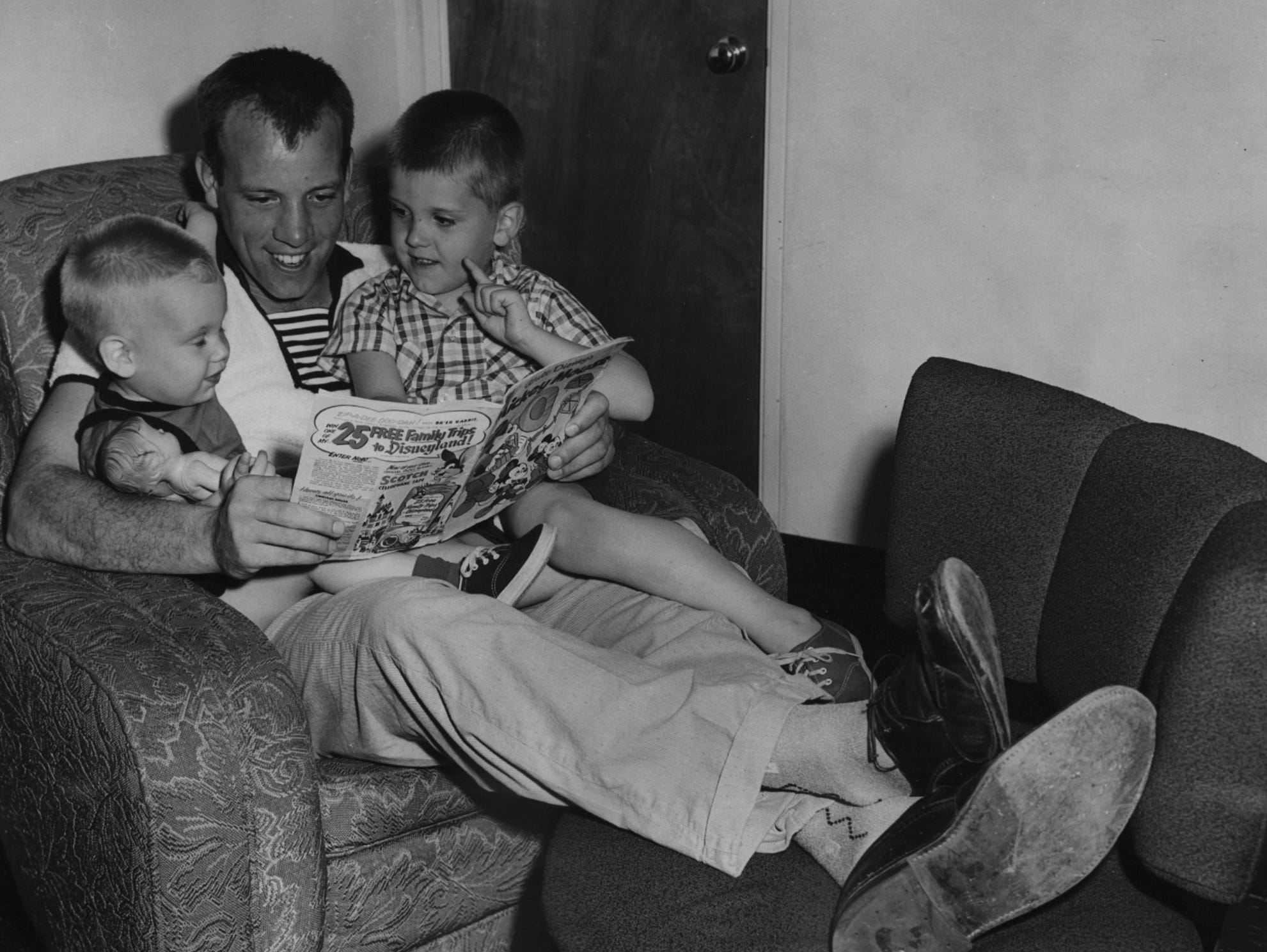 Joe Nuxhall reads to son, Kim, left, and Phillip, right.
