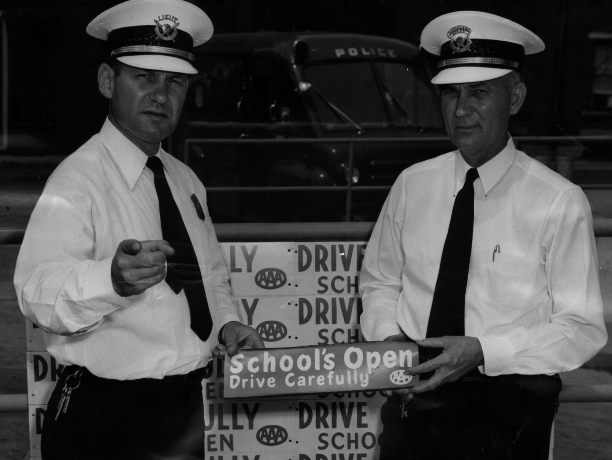 "The Cincinnati Automobile club is co-operating with the Police Department in a ""drive carefully"" campaign to warn motorists to watch out for school children. Lt. Arthur Mehring, left, and Lt. Col. Guy York, assistant chief of police, are holding one of the bumper stickers being offered free of charge by the Automobile Club. Behind them is a sample of a large cardboard sign also available at the club. Seventeen children here were killed in traffic in last year's  school period and more than 700 were injured."