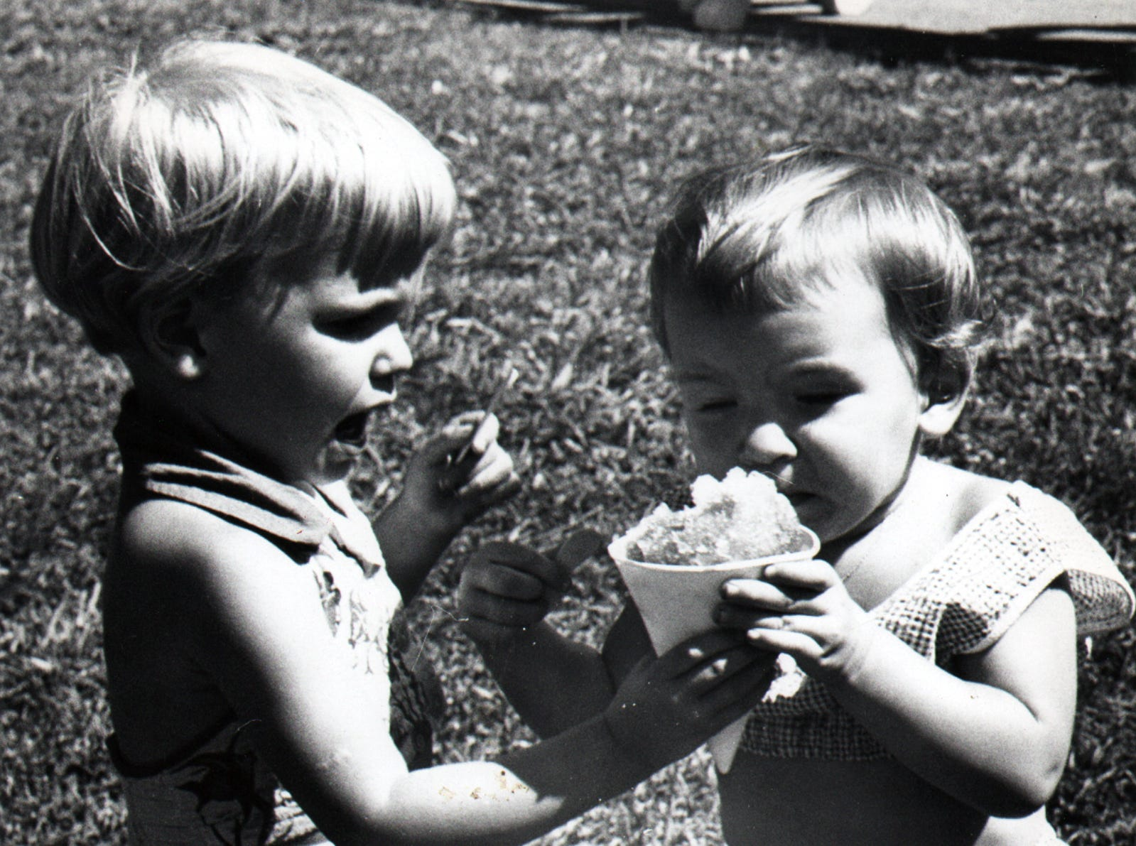 Children enjoy a snow cone during warm weather.