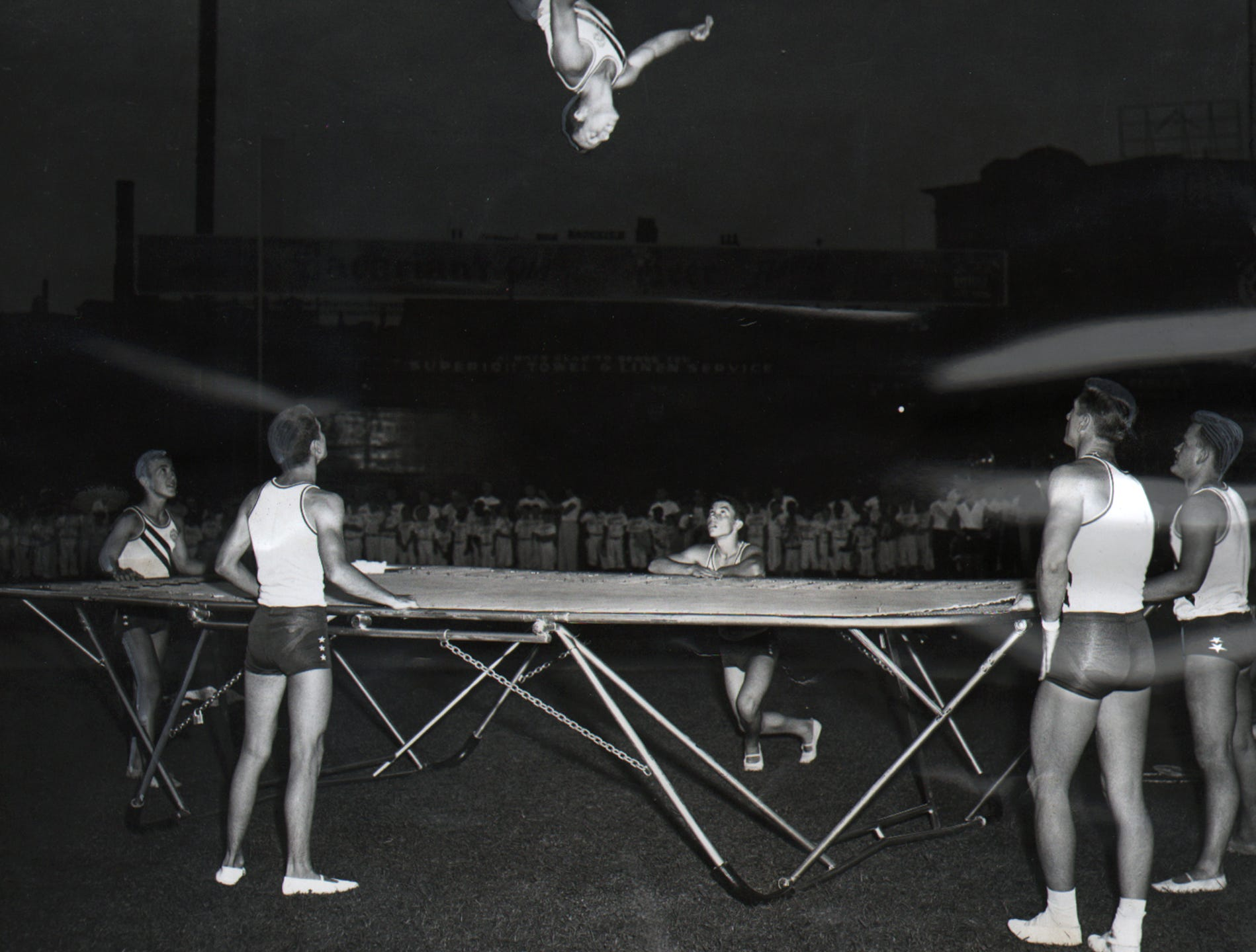 "The Hamilton High School tumbling team flips and twists for Butler County's tow ""prides,"" Joe Nuxhall, Hamilton pitcher for the Reds, and Walter Alston, manager of the Dodgers at Crosley Field."