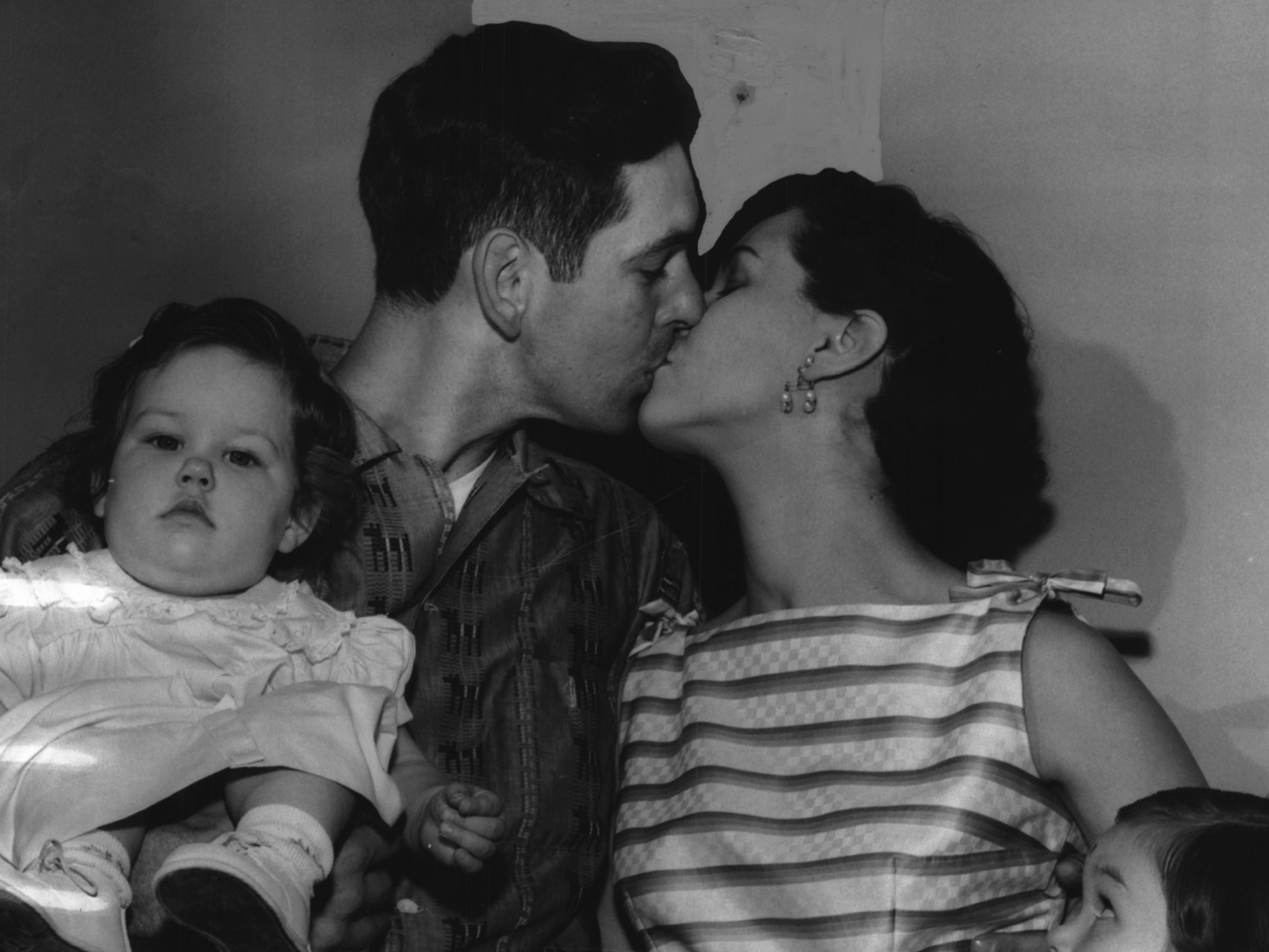 Johnny Klippstein, leaving for a day at the ball park, gets a kiss from his pretty wife Mary Ann. Watching is Mary Jo, 3. Barbara Kay, 1, showing little concern, sits on her father's arm.