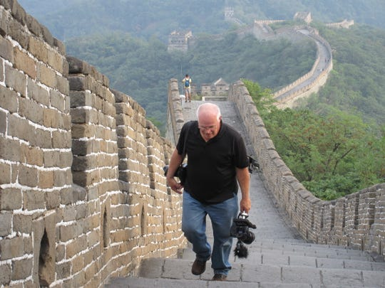 Longtime Des Moines Register photographer Rodney White walks on the Great Wall of China while on assignment in 2014.