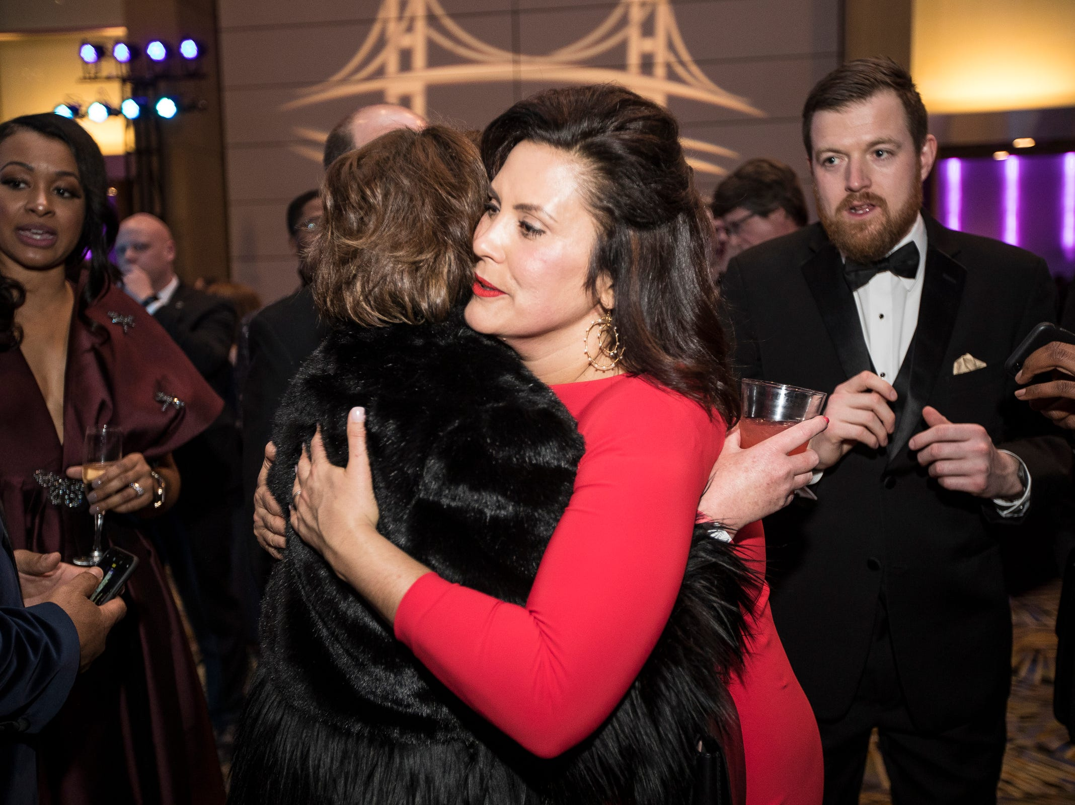 Governor Gretchen Whitmer hugs Fems for Dems steering committee member Julie Campbell-Bode during the inaugural ball at Cobo Center in Detroit on Tuesday, Jan. 1, 2019.
