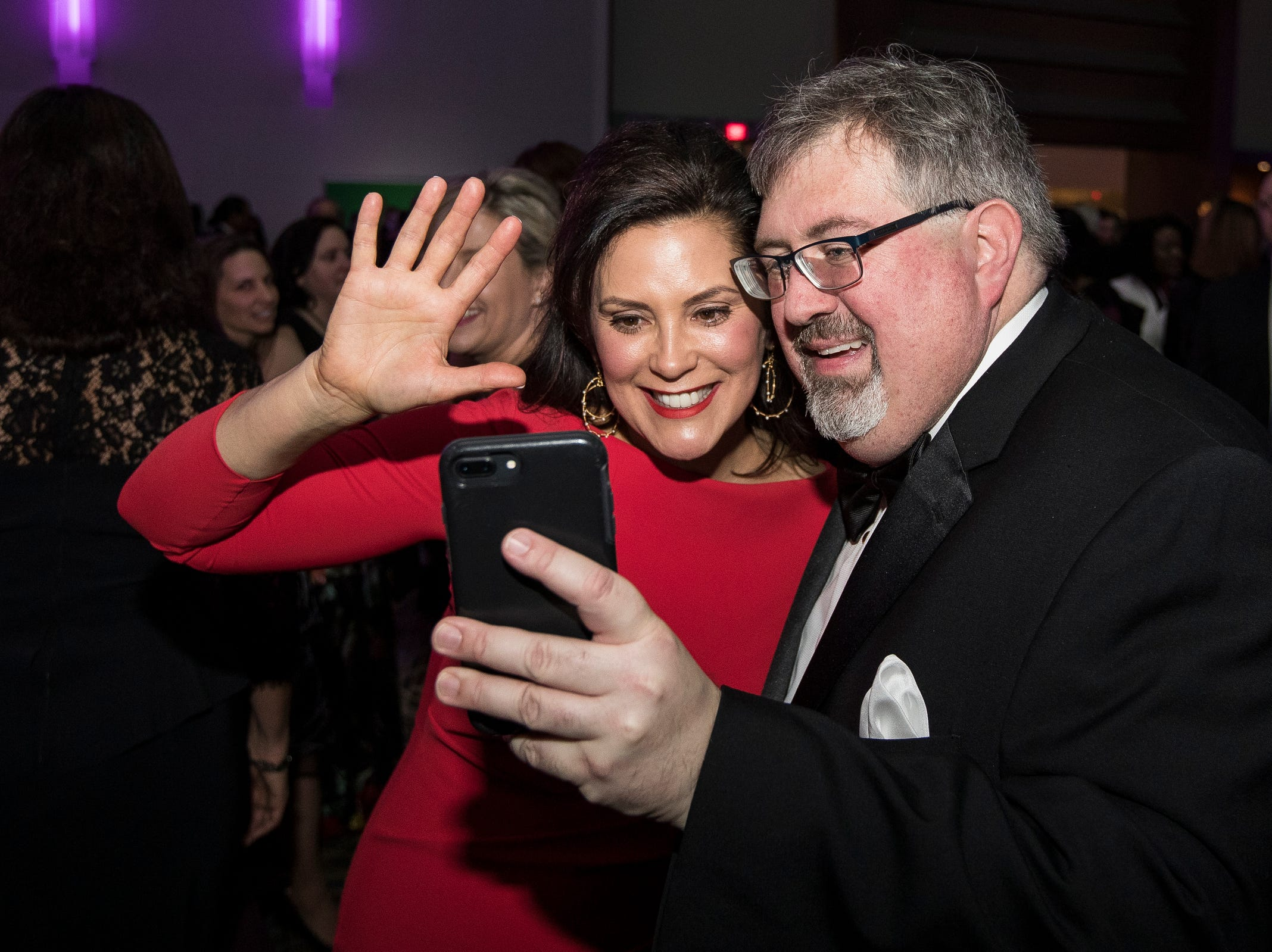 Governor Gretchen Whitmer and Todd Regis video chat with a long time friend of theirs during the inaugural ball at Cobo Center in Detroit on Tuesday, Jan. 1, 2019.