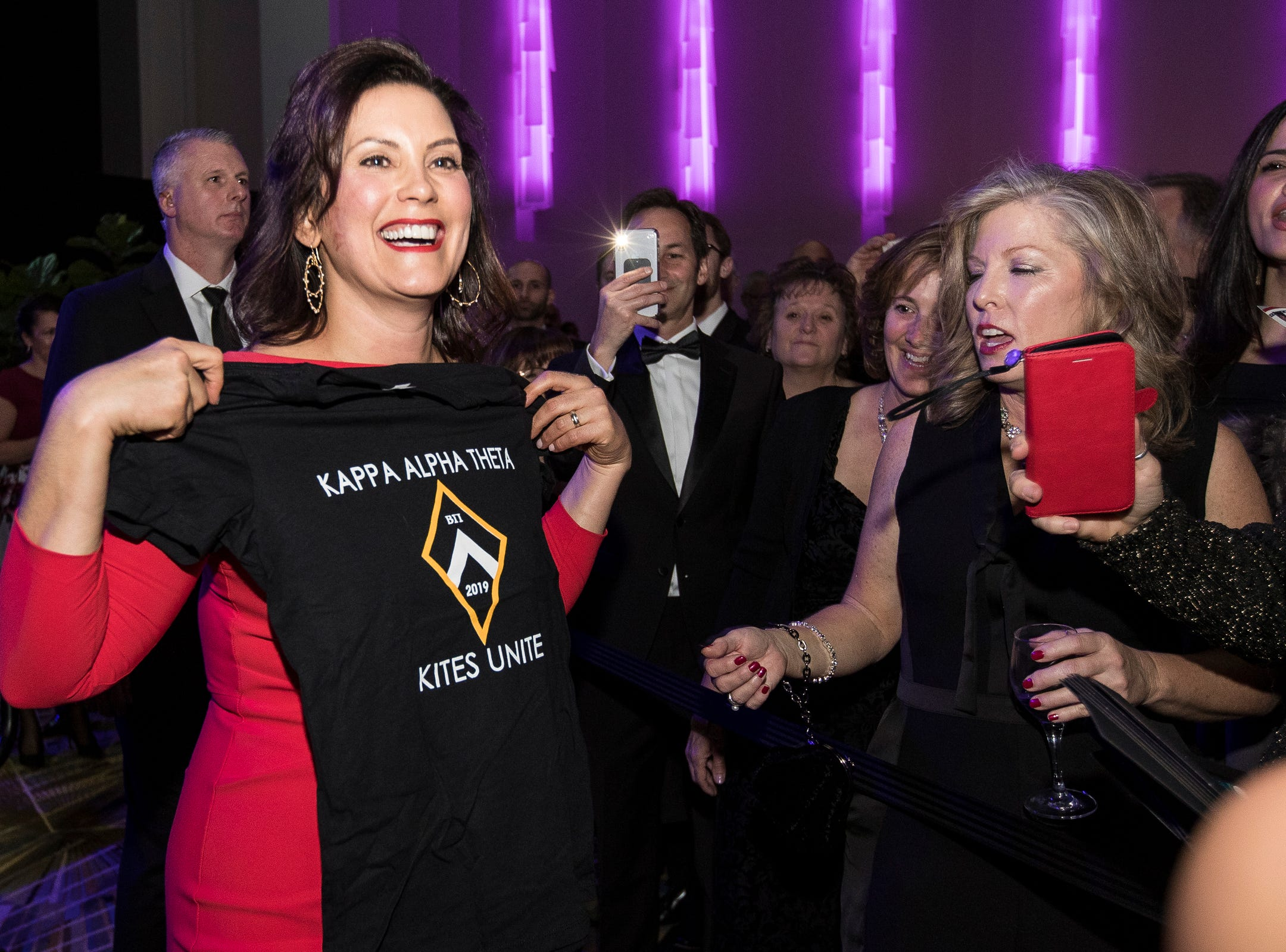 Governor Gretchen Whitmer smiles as she shows off a Kappa Alpha Theta sorority t-shirt during the inaugural ball at Cobo Center in Detroit on Tuesday, Jan. 1, 2019.