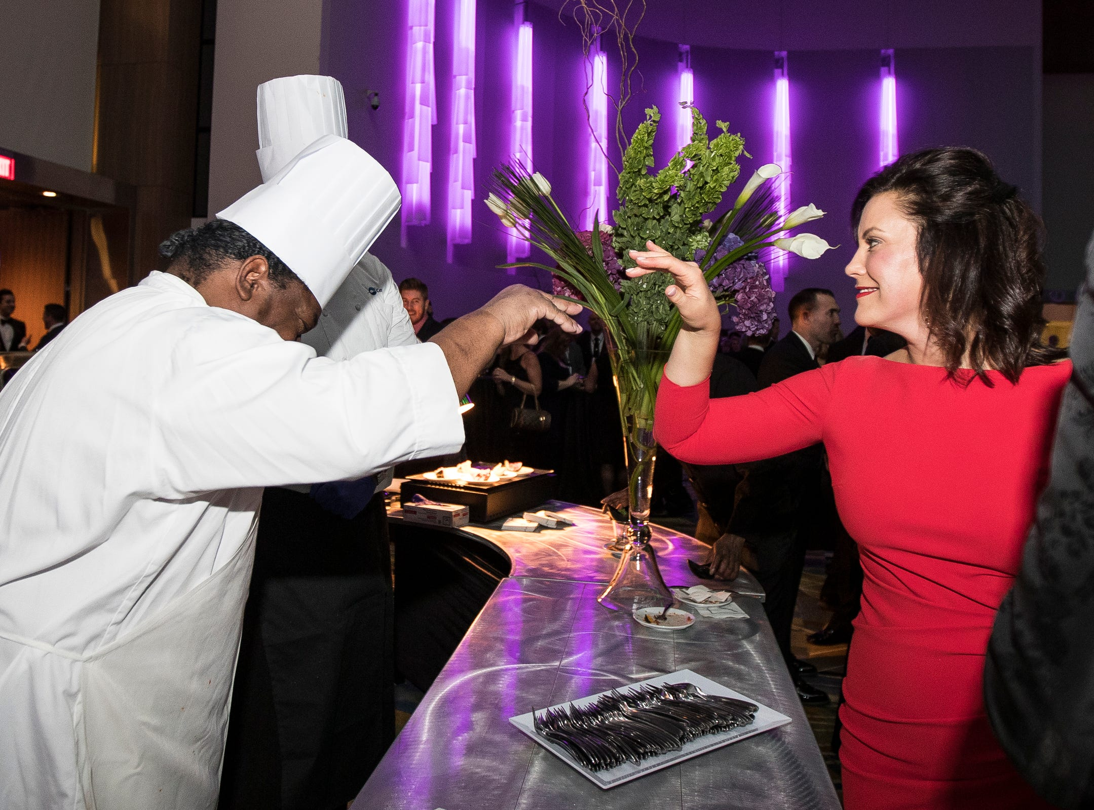 Governor Gretchen Whitmer high fives chef Guy Richards and chef Ricardo Payne during the inaugural ball at Cobo Center in Detroit on Tuesday, Jan. 1, 2019.
