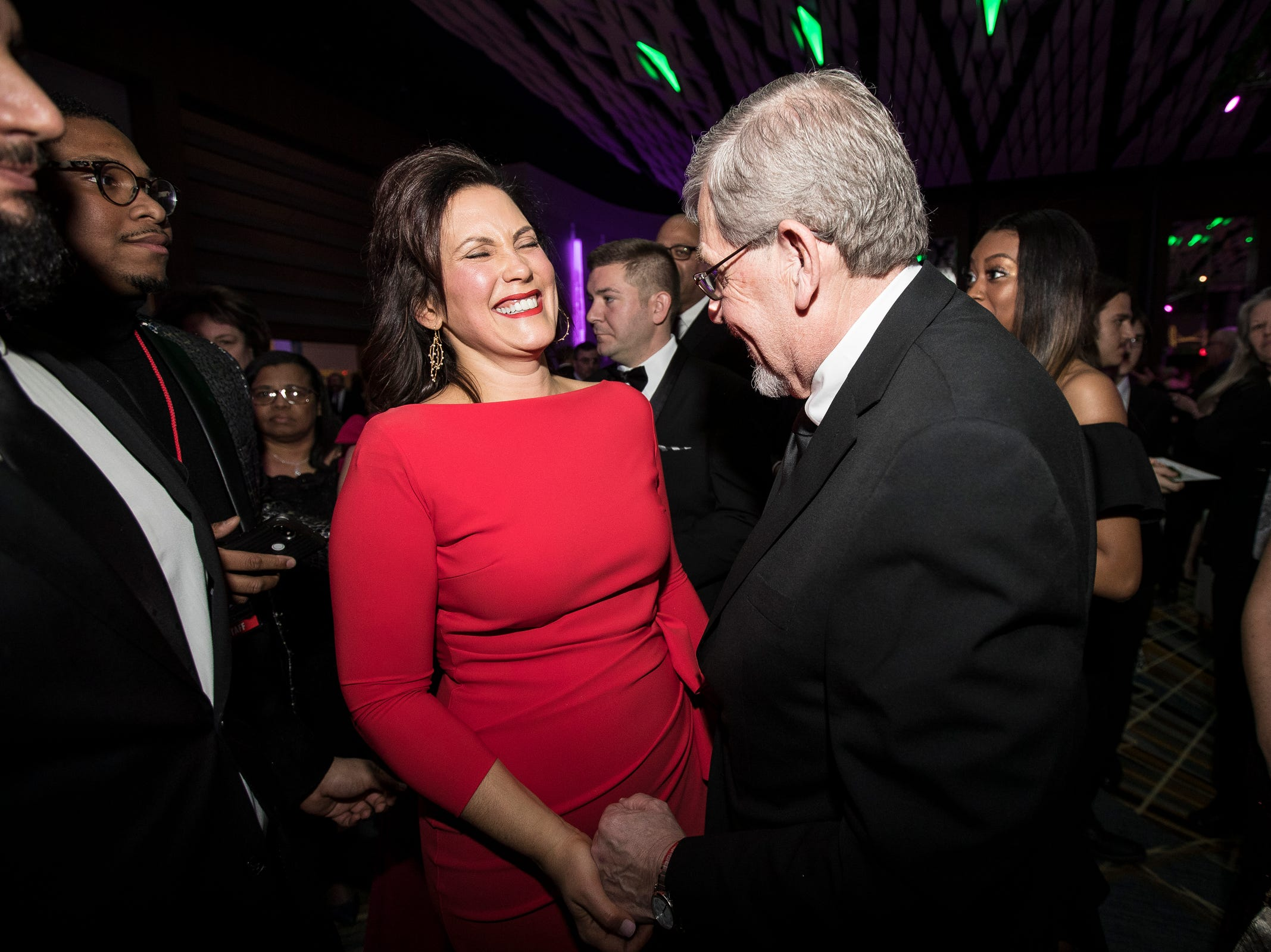 Governor Gretchen Whitmer and former state representative Stephen Adamini share a laughter during the inaugural ball at Cobo Center in Detroit on Tuesday, Jan. 1, 2019.