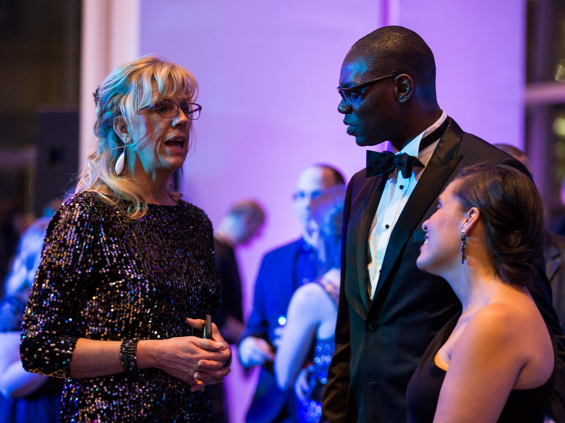 Heather Mallory-May, left, talks to lieutenant governor Garlin Gilchrist II and his wife Ellen Gilchrist during the inaugural ball at Cobo Center in Detroit on Tuesday, Jan. 1, 2019.
