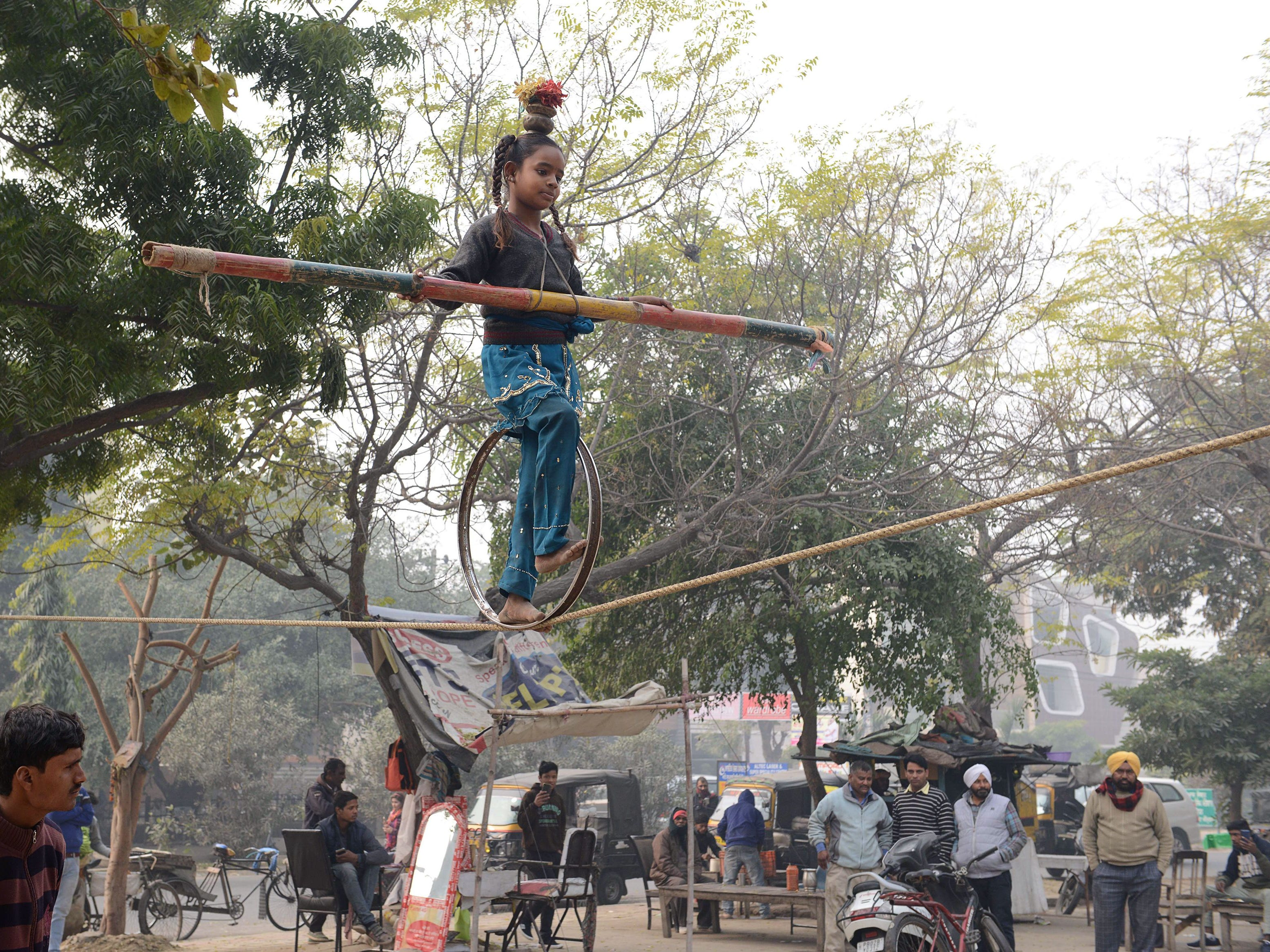Laxmi, 10, undertakes a balancing act on a rope during a street show in Amritsar, India,  on Jan. 2, 2019.  Traveling performers earn a meager income putting on such entertainment, often scouting out areas to gather a large group of onlookers, who then give money on a collection plate at the end of the show.