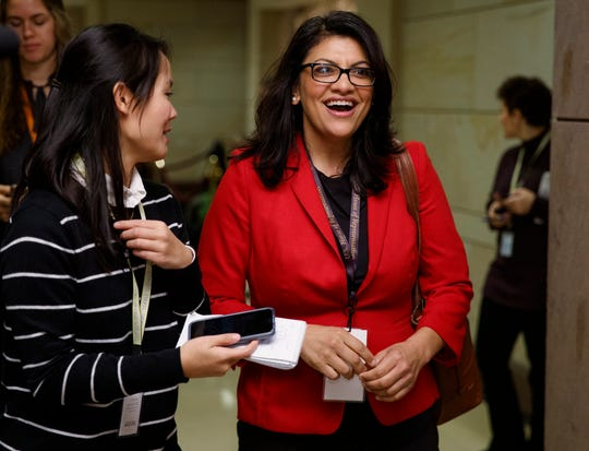 Rep.-elect Rashida Tlaib, D-Mich., right, walks with a reporter between sessions during member-elect briefings and orientation on Capitol Hill in Washington,  Nov. 15, 2018.