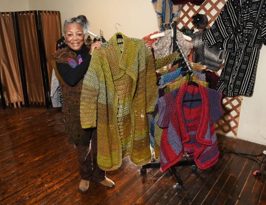 Curvie Jones, owner of Curvie's Hats, Etc., holds one of her crochet knitted jackets beside a display of vests at her Ferndale store.