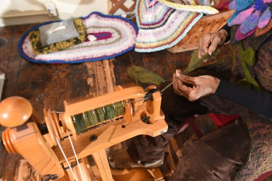 Curvie Jones, owner of Curvie's Hats, Etc., works at her spinning wheel in Ferndale as she creates yarn for projects.