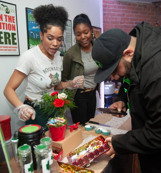 Cannabis entrepreneurs Donya Jade of Canton, left, and Adrienne Benson of Ypsilanti show party guest Gus Muffareh a gift set for cannabis users during 'The Art of Cannabis' tasting and art exhibition at the Cannabis Counsel in Detroit on  December 22, 2018.