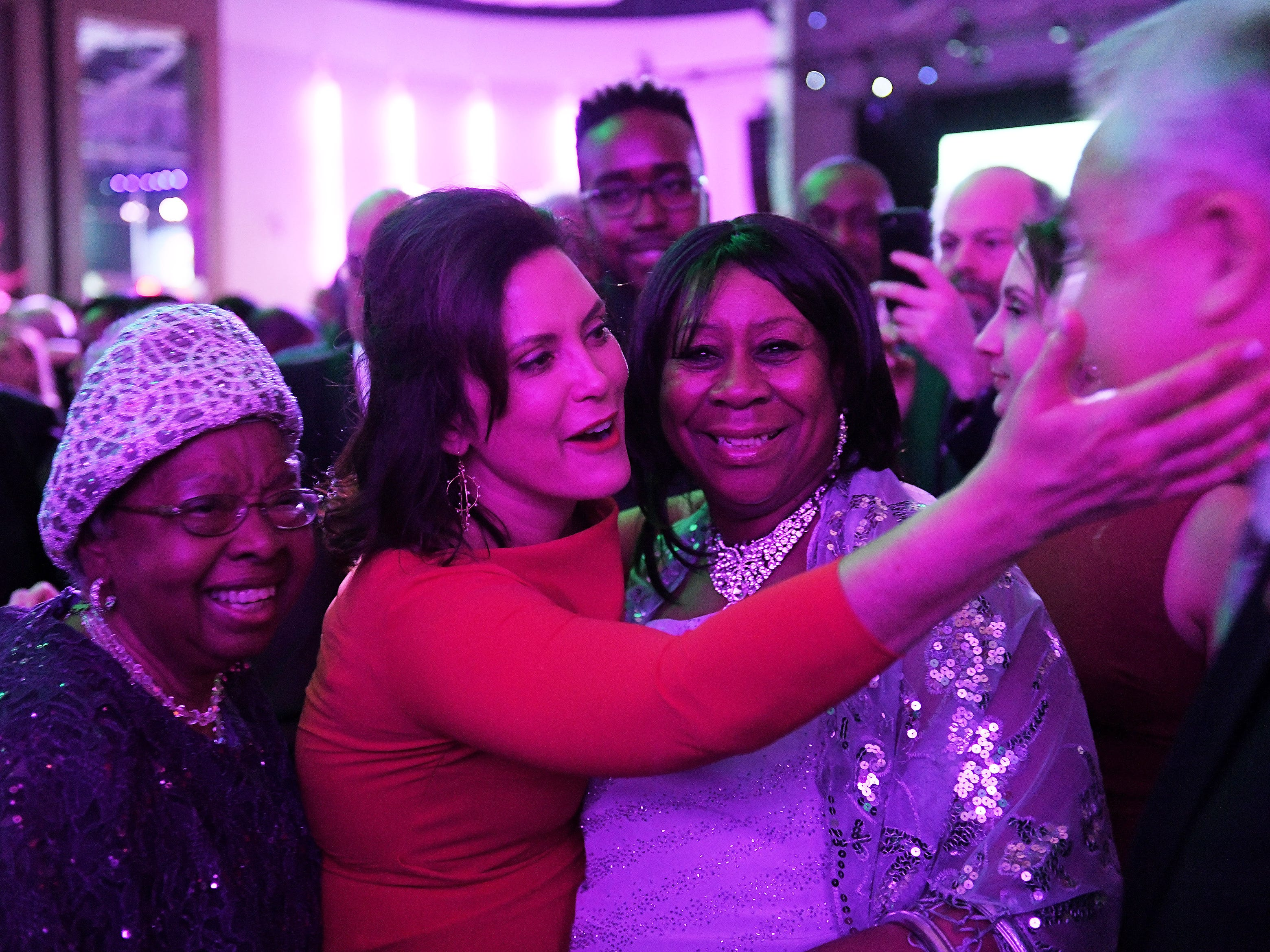 While visiting with retired state Rep. Alma Stallworth, left, and Andella White, both of Detroit, Gov. Gretchen Whitmer greets longtime friend, supporter and Wayne County commissioner Joe Palamara at the inauguration celebration in the Grand Riverview Ballroom.