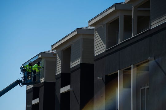 Construction crew members prep an apartment building for paint on Wednesday, Jan. 2, 2019, near the intersection of East Harmony Road and Strauss Cabin Road in Fort Collins, Colo.