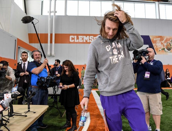 Clemson quarterback Trevor Lawrence flips his hair back as he walks in for media day in the Poe Indoor Facility in Clemson Wednesday, January 2, 2019.