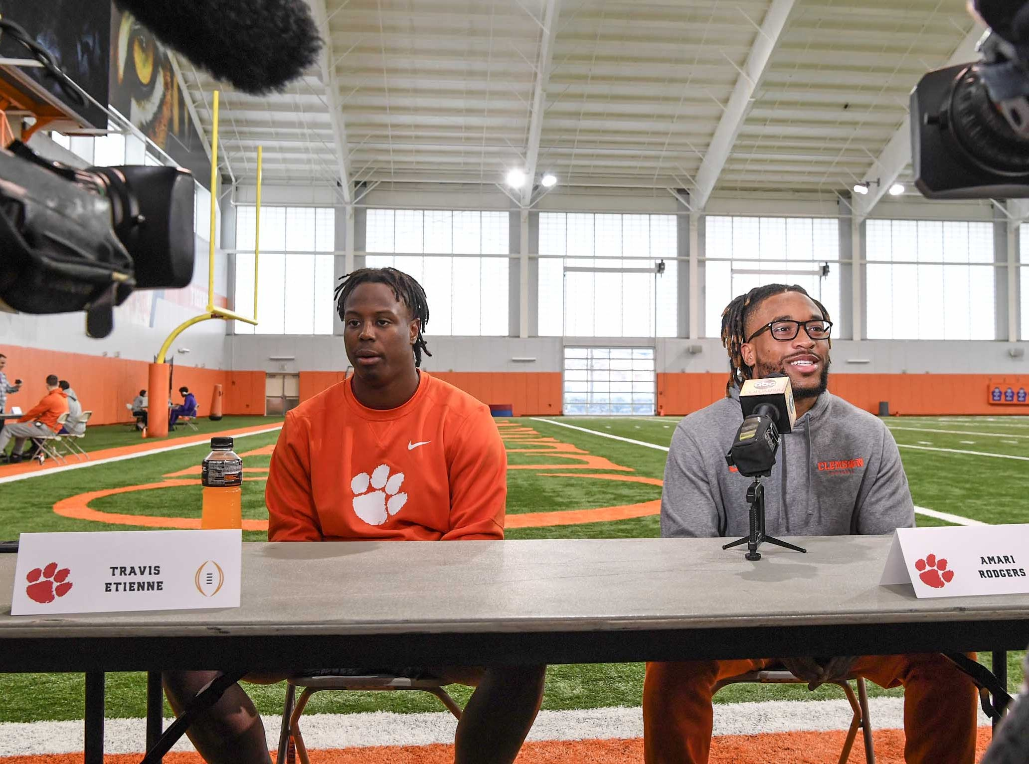 Clemson running back Travis Etienne, left, and wide receiver Amari Rodgers, right, talk during media day in the Poe Indoor Facility in Clemson Wednesday, January 2, 2019.