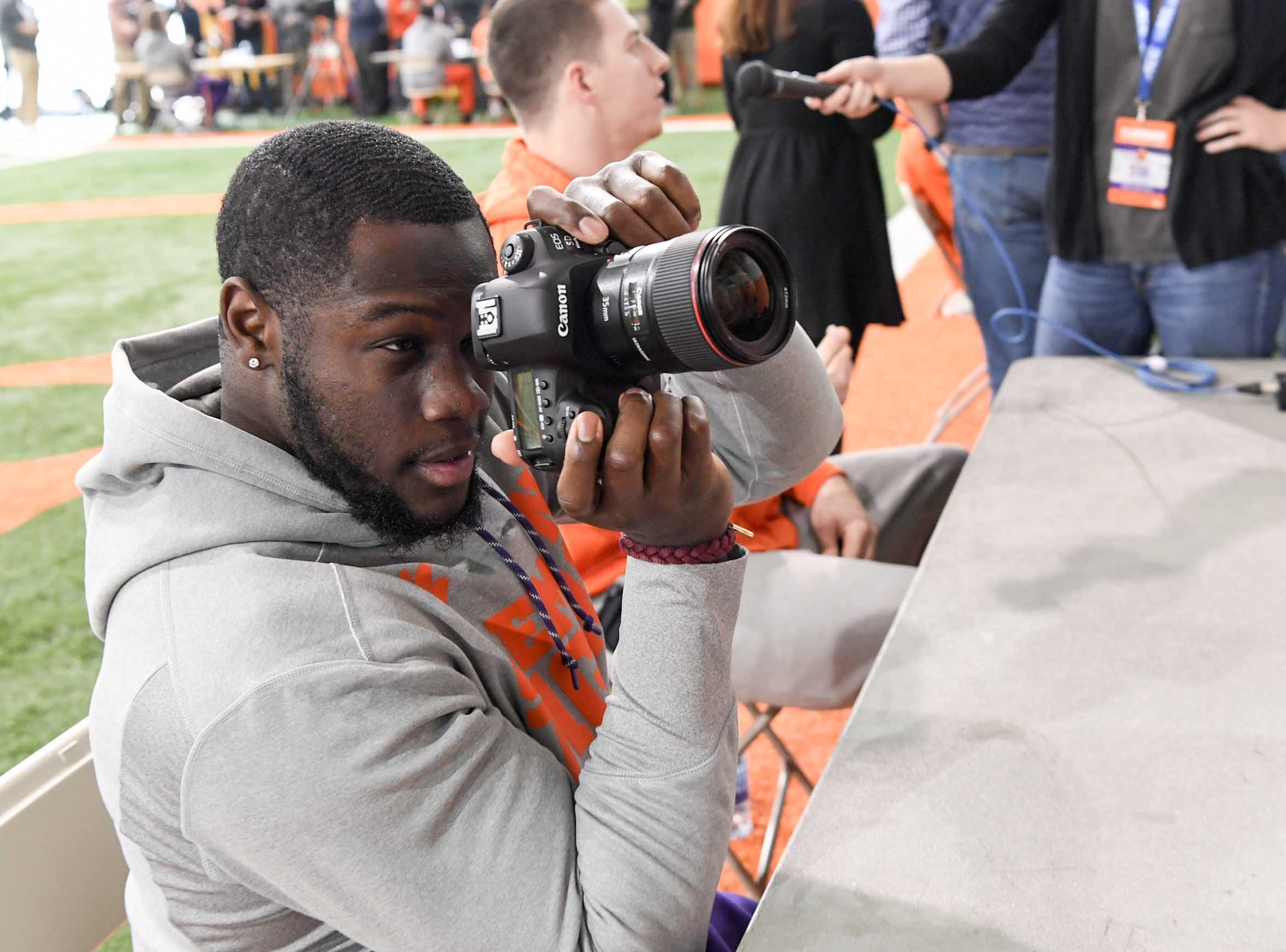 Clemson tight end Milan Richard takes a moment to get a photo of reporter Maddie Williams, a student at Clemson, during media day in the Poe Indoor Facility in Clemson Wednesday, January 2, 2019.