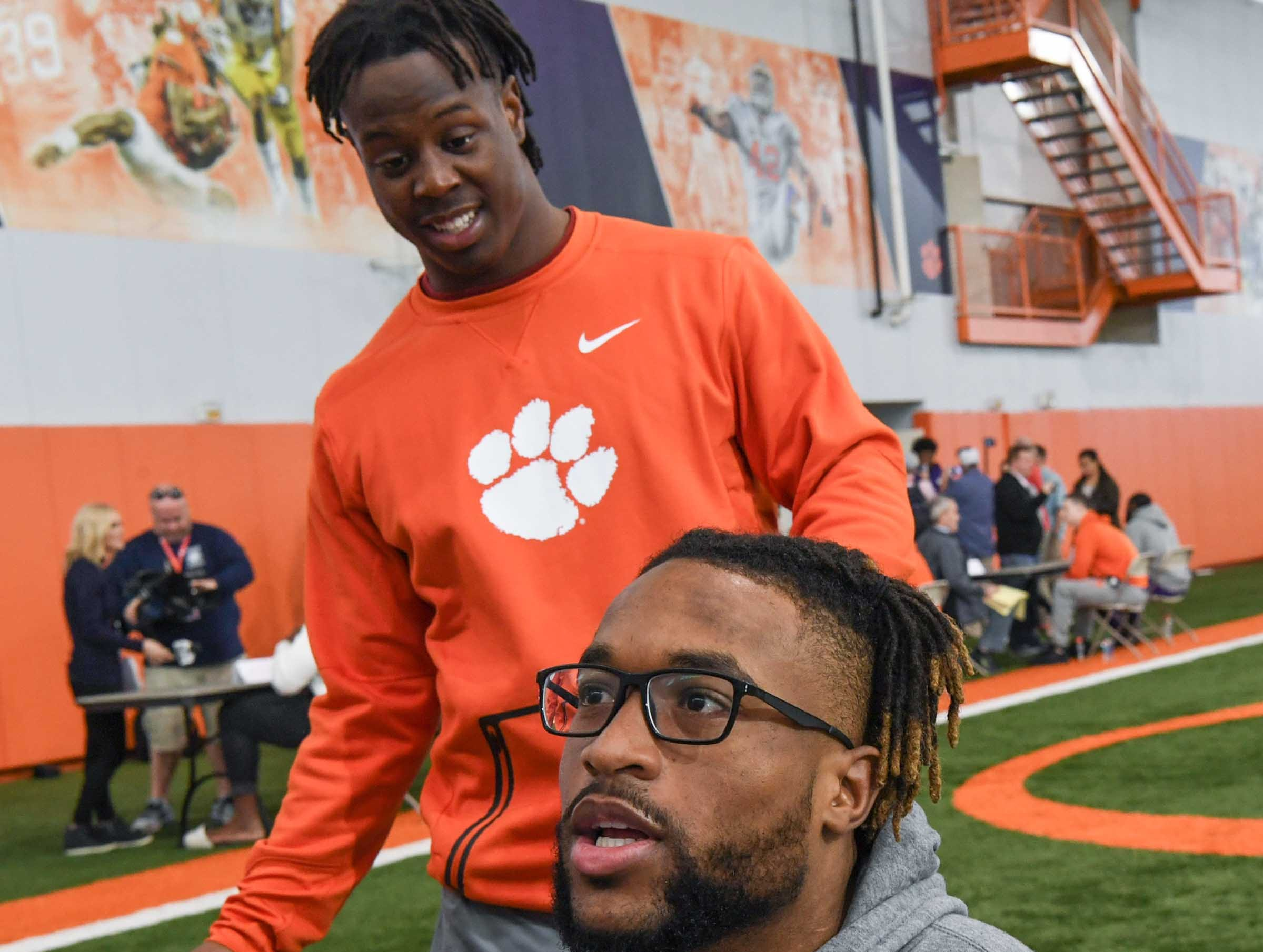 Clemson running back Travis Etienne, left, arrives to sit down while wide receiver Amari Rodgers talks during media day in the Poe Indoor Facility in Clemson Wednesday, January 2, 2019.